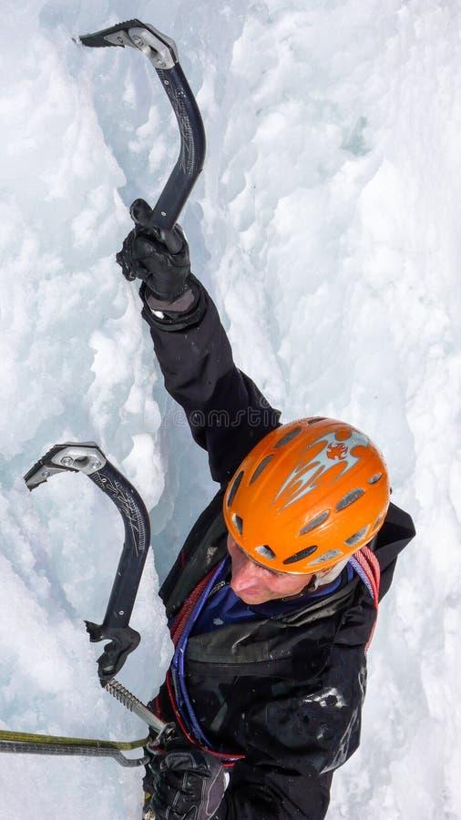 Glaciériste masculin sur une cascade congelée raide un beau jour d'hiver dans les Alpes suisses image libre de droits