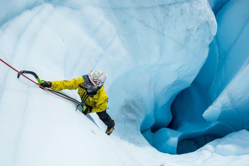 Glaciériste montant hors d'un moulin sur le glacier de Matanuska en Alaska photos libres de droits