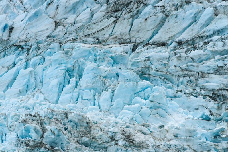 Glacial blues and dirt browns in fractured ice patterns on glacier in Drygalski Fjord, South Georgia, as a nature background stock photography