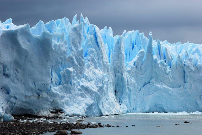 Glacial ice Perito Moreno Glacier seen from Argentino Lake - Argentina. Light blue glacial ice field Perito Moreno Glacier with dark clouds seen from Argentino stock photos