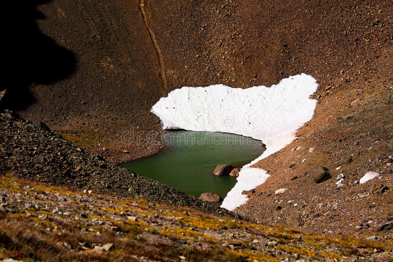 Glacial pond in the Rocky Mountain National Park. Snow on the banks of an emerald green glacial pond in the high peaks of the Rocky Mountain National Park stock images