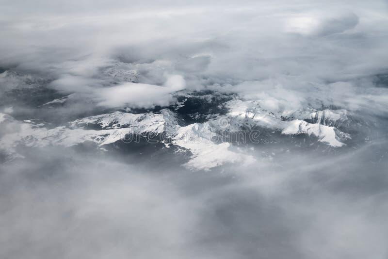 Glaciares alpinos del avión en día nublado fotos de archivo