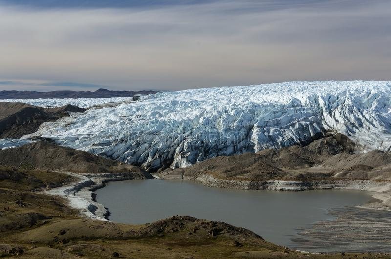 Glacier front with crevasses and a silt lagoon, Point 660, Kangerlussuaq, Greenland. Glacier front with crevasses and a glacial lagoon full of silt, Point 660 stock photos