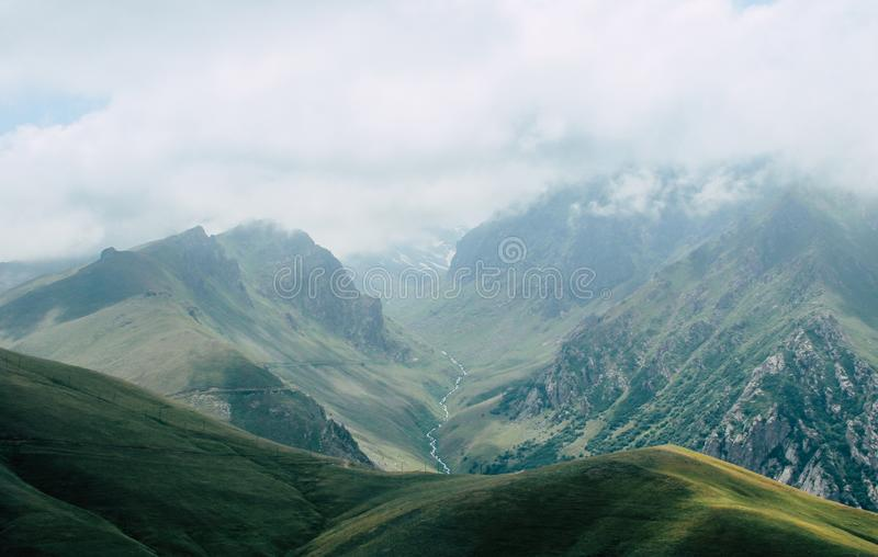 Glacier in a green Valley and clouds in the mountain royalty free stock image