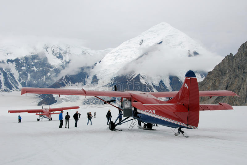 Glacier landing with aircraft in Talkeetna mountain range - Alaska. Landing with red aircraft on glacier with mountains and snow in Talkeetna mountain range royalty free stock images