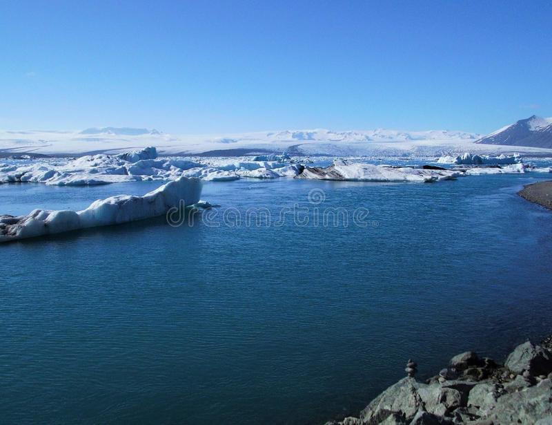 Beautiful Natural Floating Blue Icebergs On Blue Lagoon And Mountains View. Beauty of nature Floating blue ice and iceberg with mountains view. blue lagoon blue stock photo