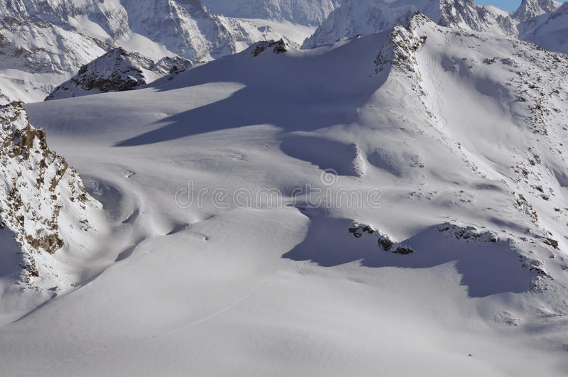 Glacier skiing. Helicopter skiing in the swiss alps. Ski tracks left in fresh powder snow on the Rosablanche royalty free stock photography