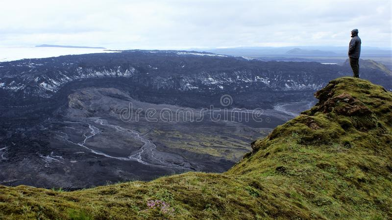 Glacier view atop rugged Iceland mountain hike. Lone hiker contemplates the vastness and gargantuan scale of the mountain range, glacier, and debris field to his royalty free stock photos