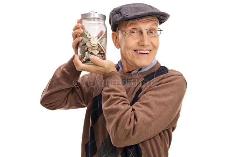 Glad äldre man som rymmer en krus med pengar royaltyfri foto