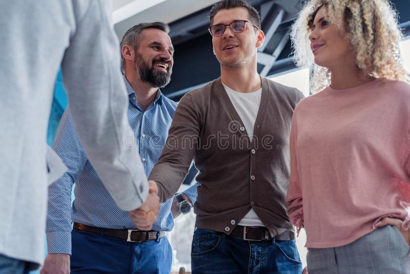 Glad στην εργασία με σας! Νέα σύγχρονα άτομα στα έξυπνα χέρια τινάγματος περιστασιακής ένδυσης και χαμόγελο εργαζόμενα στο δημιου στοκ εικόνες