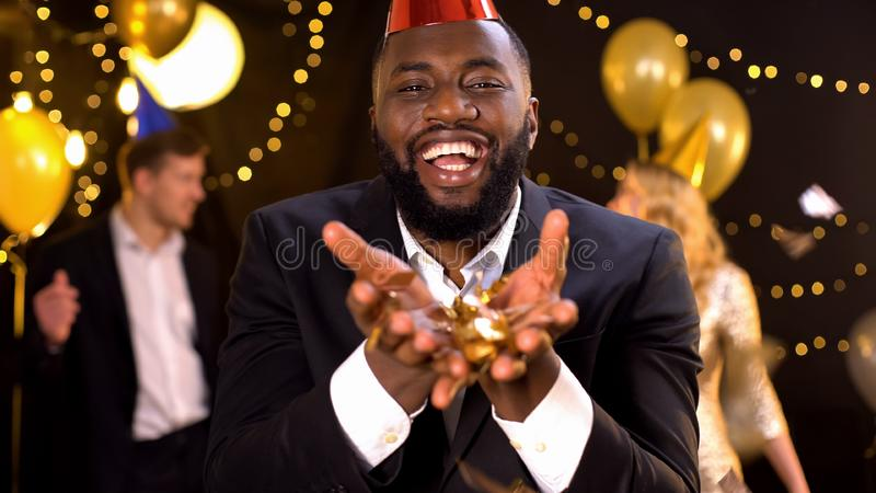 Glad african american holding gold confetti and smiling at camera, celebration. Stock photo royalty free stock photo