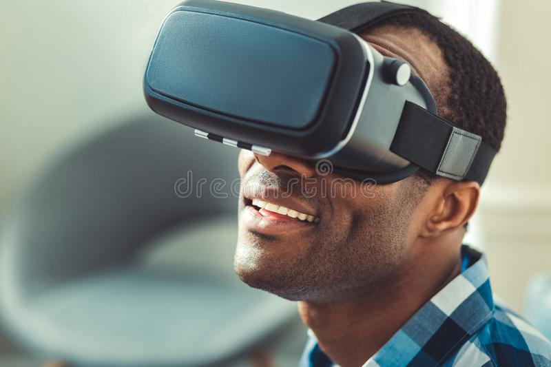 Glad afro american man tuning VR headset. High resolution. Amazed afro american man putting on VR glasses and opening mouth stock images