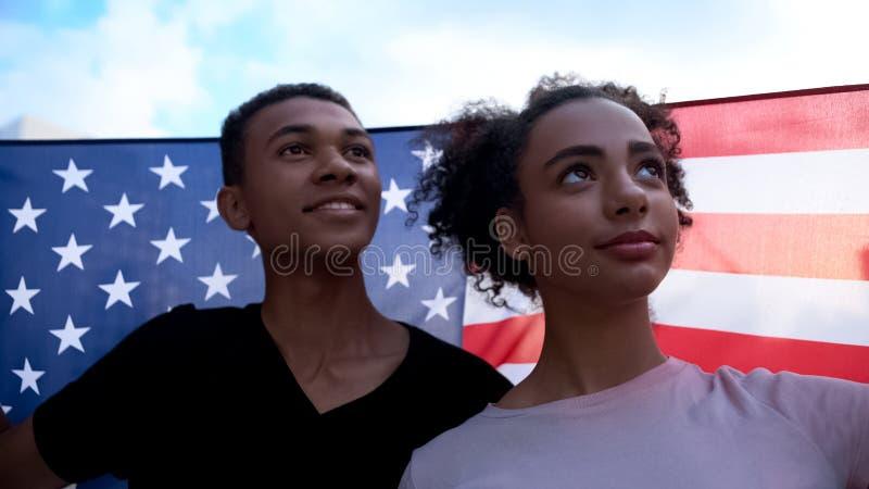 Glad afro-american teen couple waving USA flag, celebrating national holiday stock photos