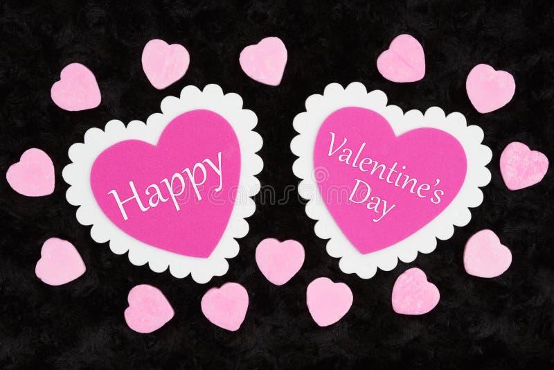 Glad Alla hjärtans dag hälsas med vita och rosa hjärtan och godis på svart fotografering för bildbyråer