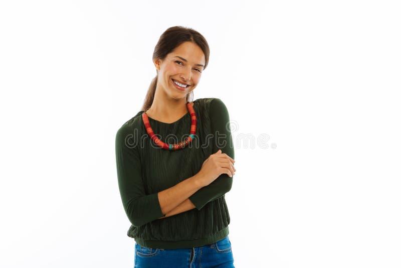 Glad angenäm ung kvinna som ler till dig arkivbild