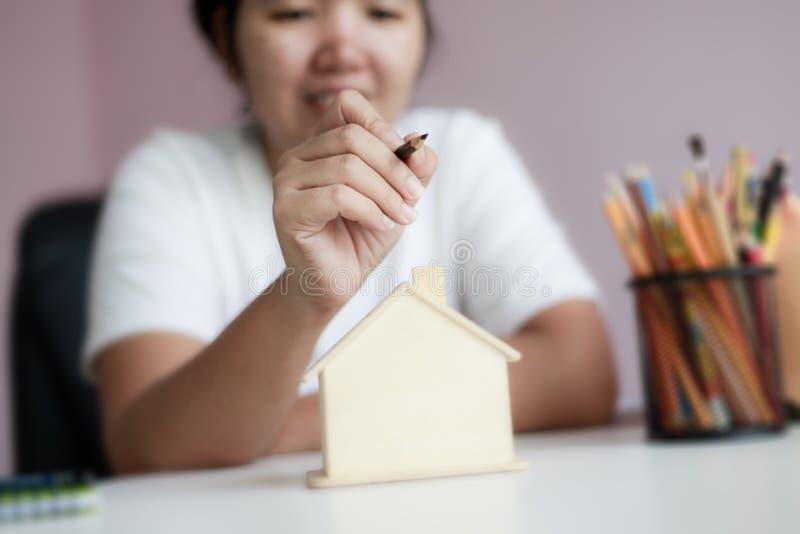 Glad asiatisk kvinna som använder pennritning och planerar med trähuspigg-bankmetafor som planerar att spara pengar för att kö fotografering för bildbyråer