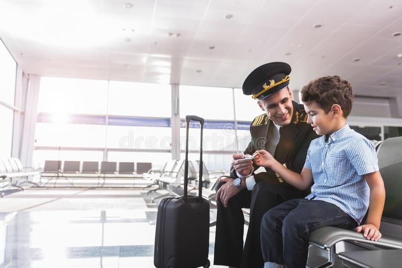 Glad aviator with son in airport royalty free stock images