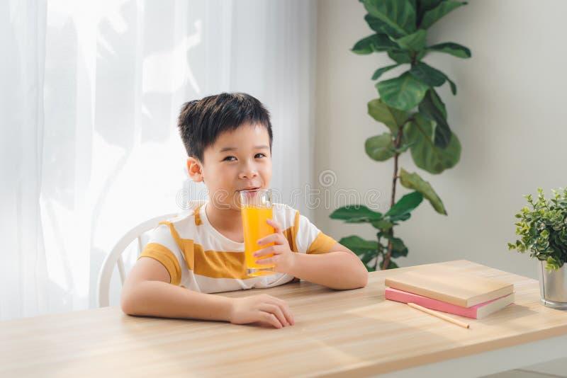 Glad barnslig apelsinjuice, sittande vid ett bord och leende royaltyfria bilder