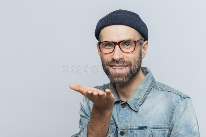 Glad bearded male in trendy eyewear expresses his love, shows ai stock photos