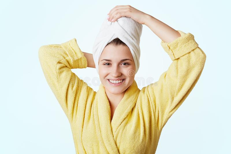 Glad beautiful female wears bathrobe and towel on head, glad to take shower, has appealing appearance, stands against white backgr stock photography