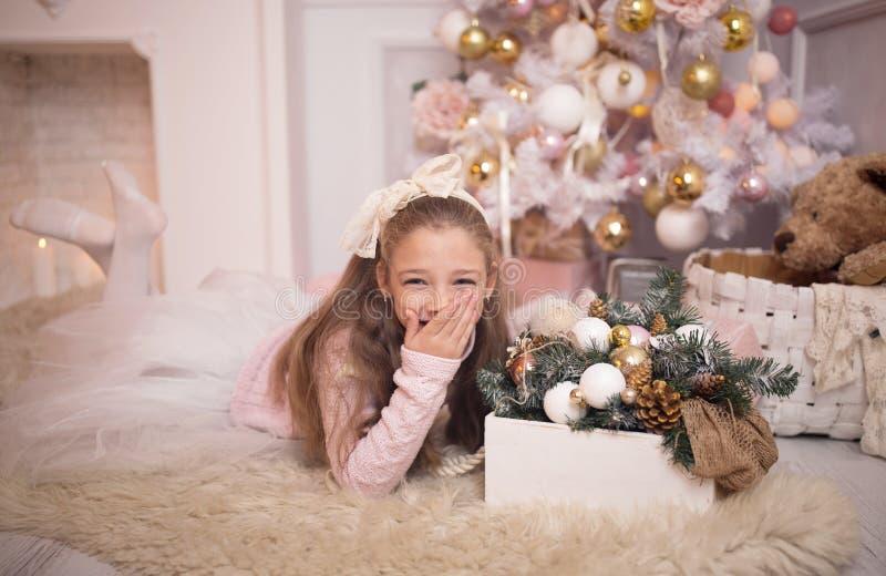 glad berömjul Härlig liten flicka i en klänning som ligger nära julgranen arkivbild