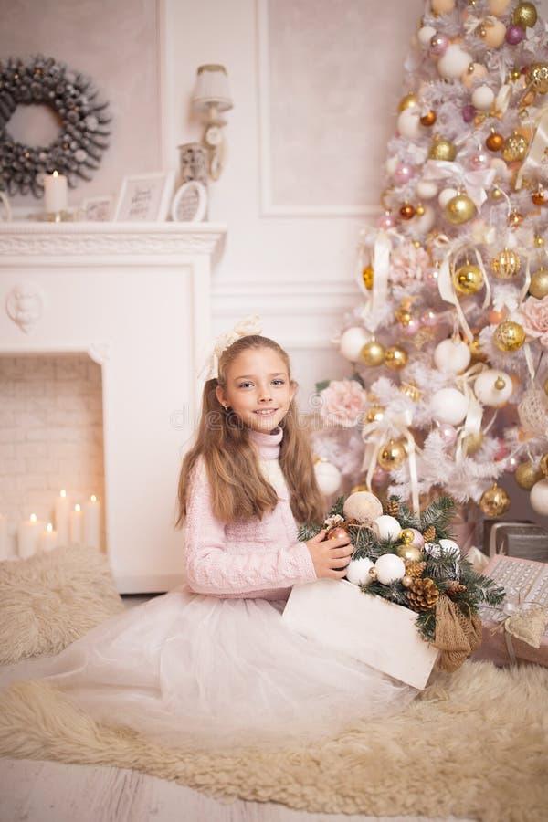 glad berömjul Härlig liten flicka i en klänning som sitter nära julgranen royaltyfri foto