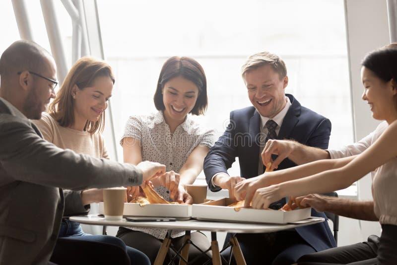 Glad blandning av rasarbetare som delar lunch, äter pizza arkivfoton