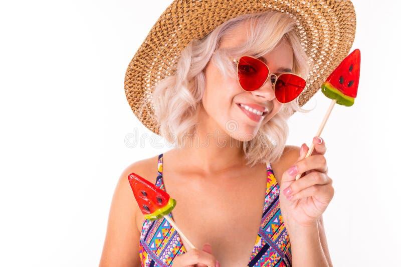 Glad blond kaukasisk hona i baddräkt med vattenmelonlolipoppar och sjömil isolerade på vit bakgrund arkivbild