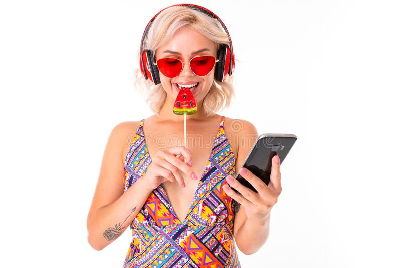 Glad blond kaukasisk hona i baddräkt med vattenmelonlolipoppar, telefon och sjömil isolerade på vit bakgrund fotografering för bildbyråer