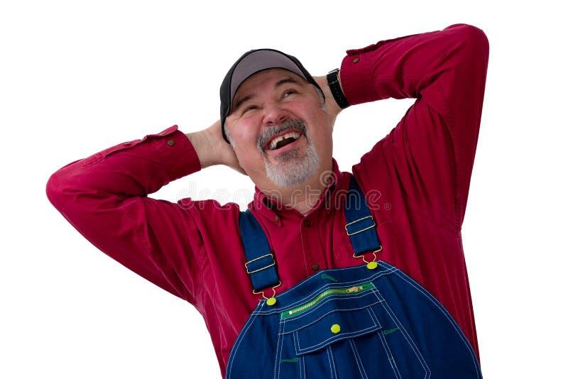 Glad bonde eller arbetare som skrattar i fröjd royaltyfri foto