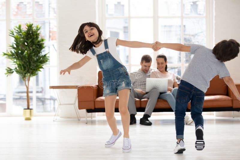 Glad bror och syster med händer och spin royaltyfri fotografi
