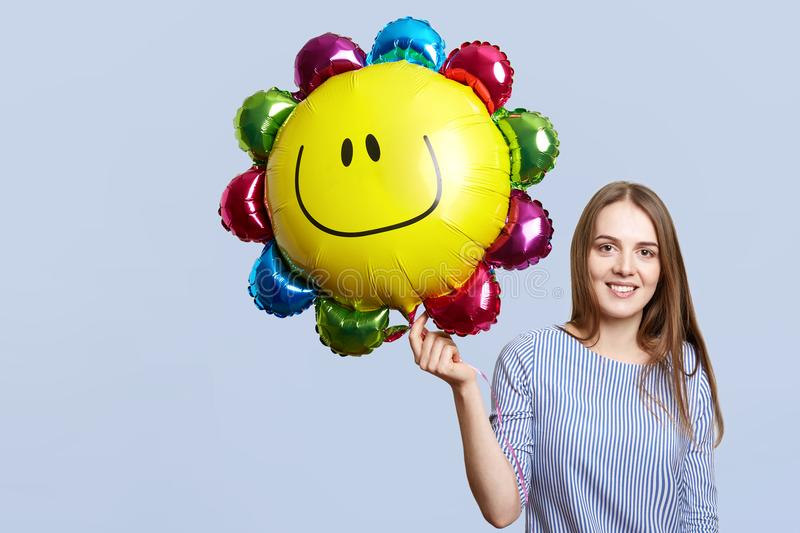 Glad brunette woman wears striped blouse, holds balloon, happy to celebrate daughter`s birthday, meets guests, isolated over blue royalty free stock photo