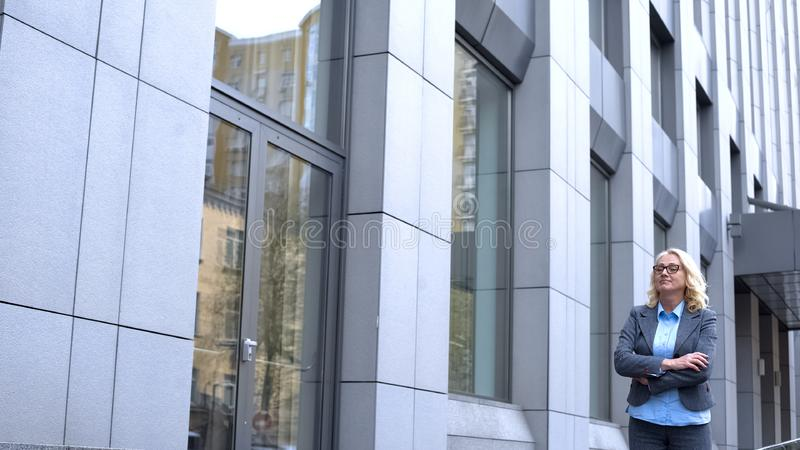 Glad business woman with folded arms standing outdoors office building, career stock photos