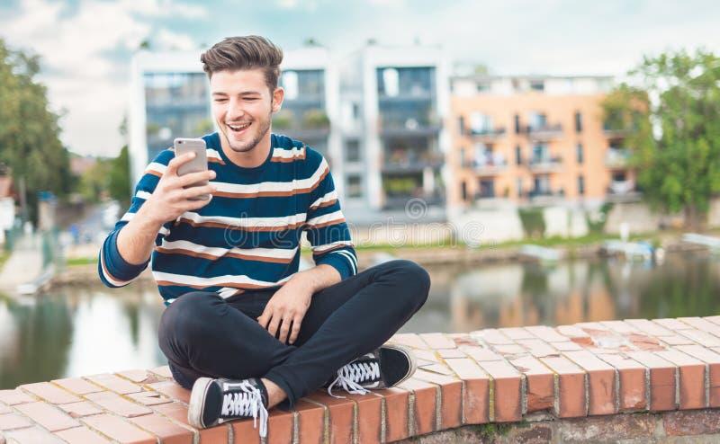 Glad caucasian stilig man med skäggstubb genom att använda mobiltelefonen royaltyfri fotografi
