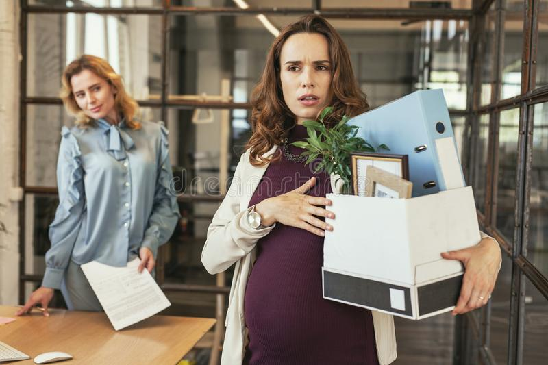 Glad colleague seeing off pregnant boss stock image