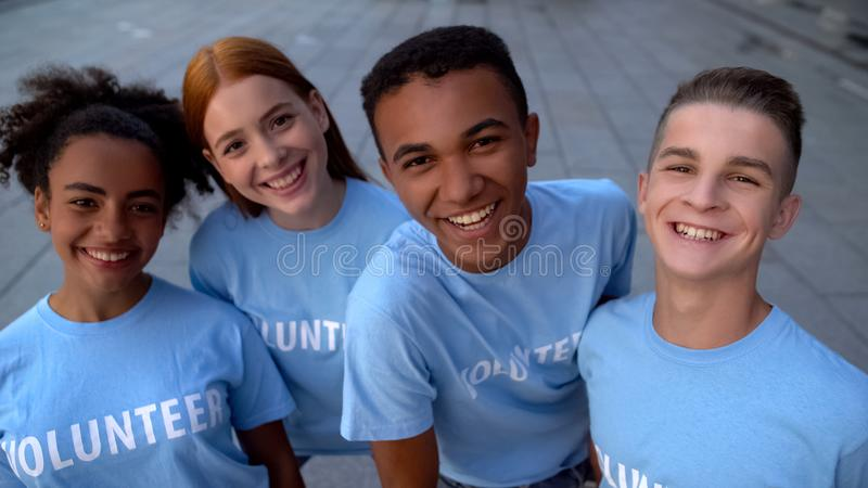 Glad college students in volunteer t-shirts looking camera, support togetherness royalty free stock photos