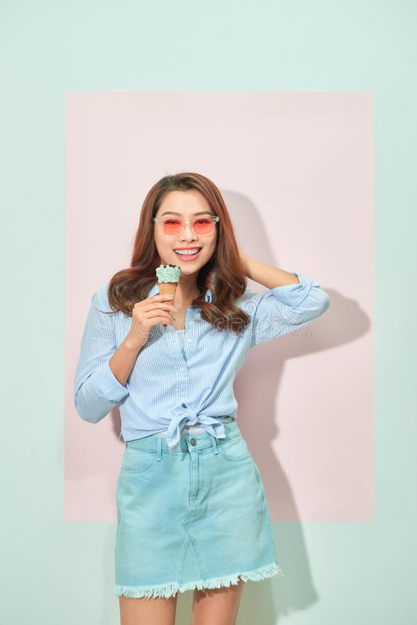Glad delightful young asian woman with toothy smile looks at camera, holds tasty ice cream, stands on light pink background in royalty free stock image
