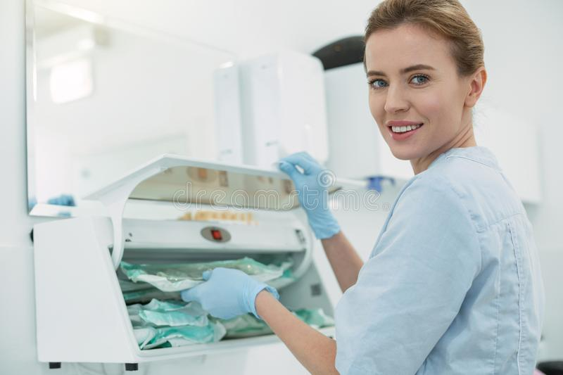 Glad dentist holding some instruments royalty free stock photos