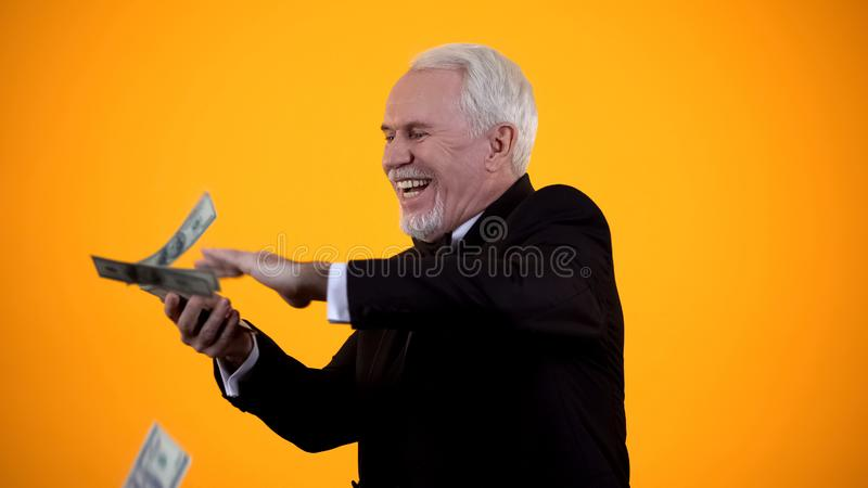Glad elderly person in suit throwing dollar notes and smiling, good income, win stock images