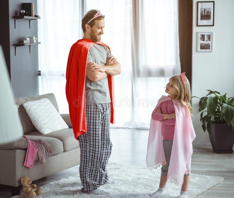 Glad fader och dotter som hemma spelar i kungarikelek royaltyfria foton