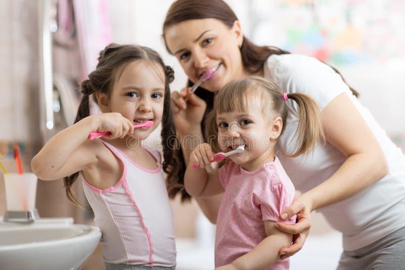 Glad familj borstar tänderna royaltyfria bilder