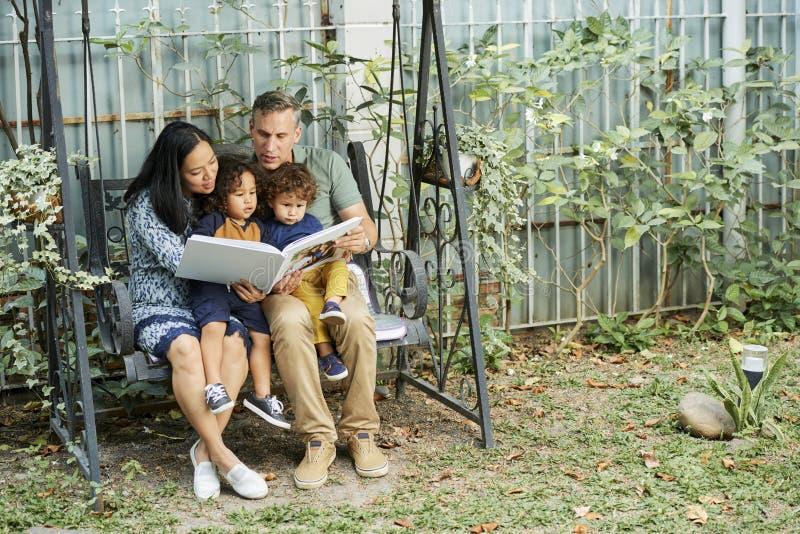 Glad familj med att intressera boken arkivfoto