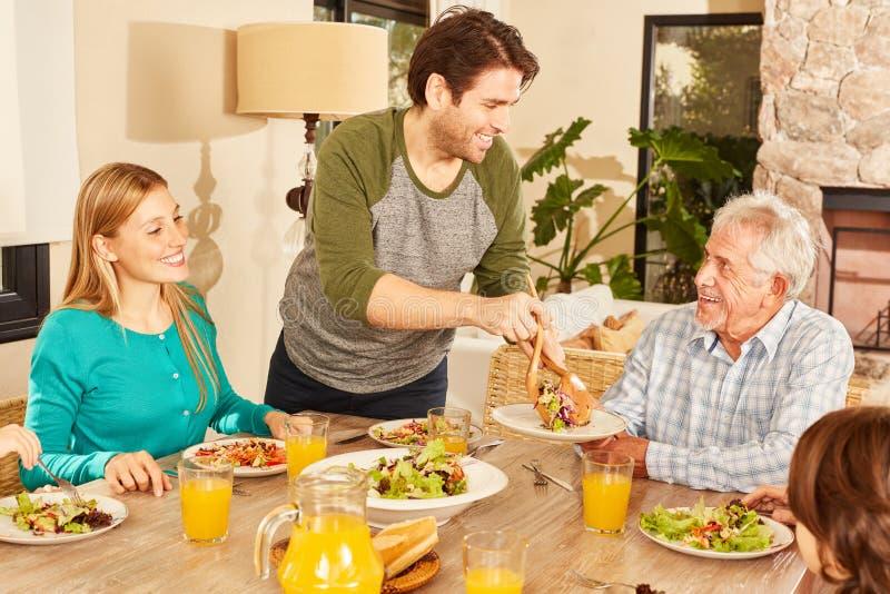 Glad familj med farfar som åt middag royaltyfri foto