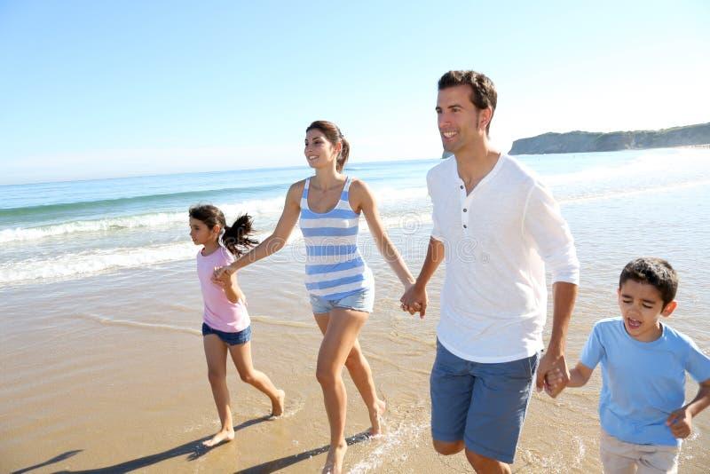 Glad familj som har gyckel på stranden arkivfoton