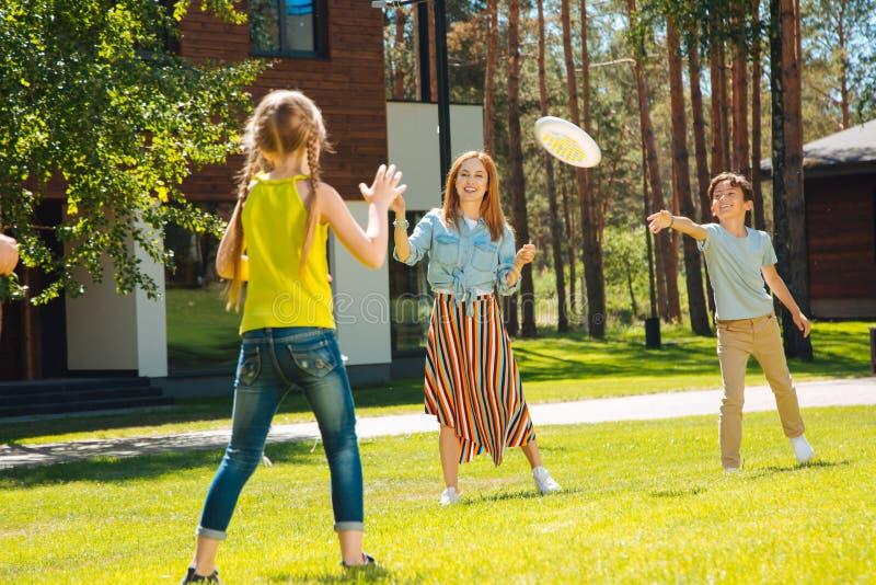 Glad familj som spelar en lek i gården fotografering för bildbyråer