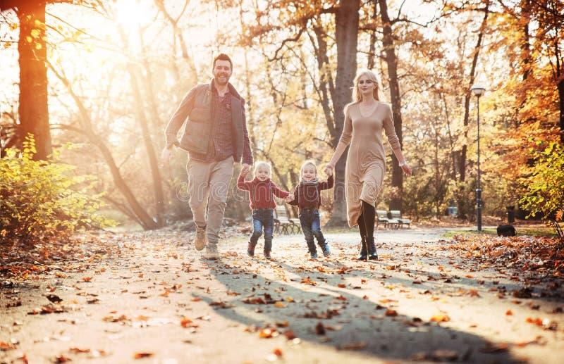 Glad familj som tycker om stort höstligt väder royaltyfria bilder