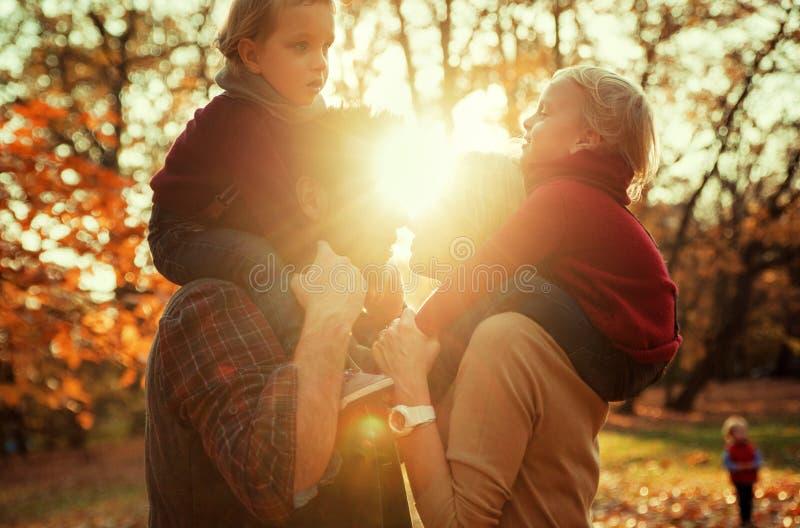 Glad familj som tycker om stort höstligt väder fotografering för bildbyråer