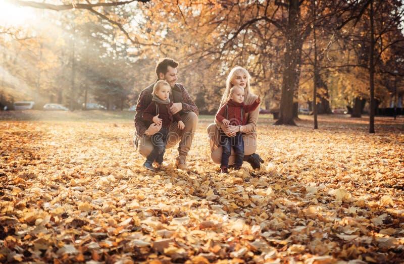 Glad familj som tycker om stort höstligt väder arkivfoto