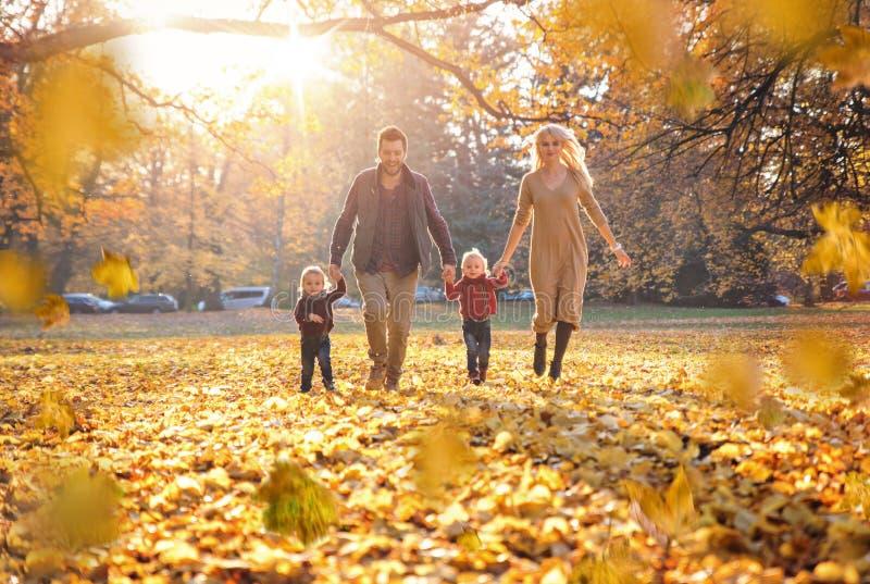 Glad familj som tycker om stort höstligt väder royaltyfri fotografi
