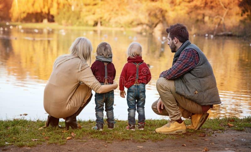 Glad familj som tycker om stort höstligt väder arkivfoton